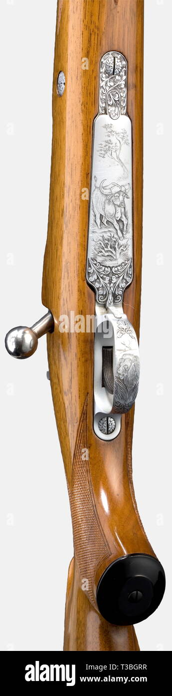 "An FN Browning repeating rifle, 10.75 x 68 calibre. No. B 58353. Flawless, completely blued barrel with bright bore. Length 60 cm. Mauser 98 action. Side safety. Hinged magazine floor plate. Crisp trigger pull. Magazine floor plate and trigger guard display restrained, hand engraved buffalo and lion in a landscape between decorative plants, signed ""Vandermissen"". Outstanding lacquered light walnut stock with sharp chequering, cheekpiece, ventilated recoil pad, and two sling swivels. Length from trigger to the centre of the recoil pad: 35 cm. Fixe, Additional-Rights-Clearance-Info-Not-Available Stock Photo"