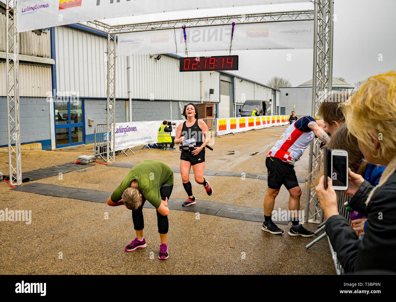 Two amateur runners, a middle aged lady and man, stopping to catch their breath, have a stretch and recover after completing the Norwich half marathon - Stock Image