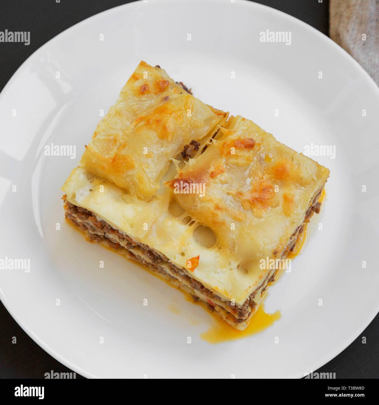 Traditional Beef Lasagne On A White Round Plate Over Black