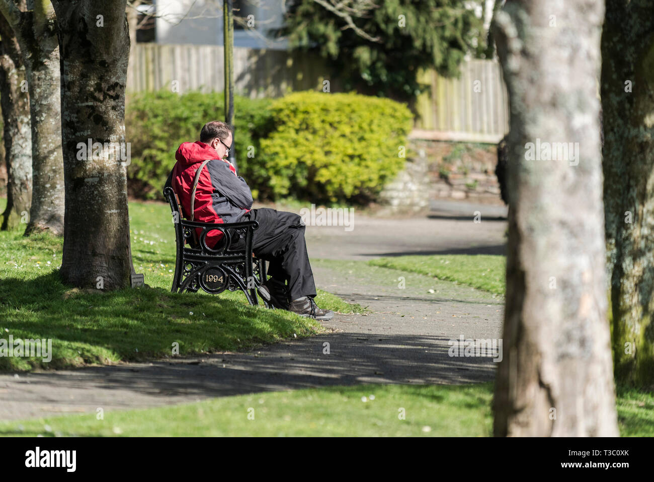 A man sitting in silent contemplation on a park bench in Trenance Gardens in Newquay in Cornwall. - Stock Image