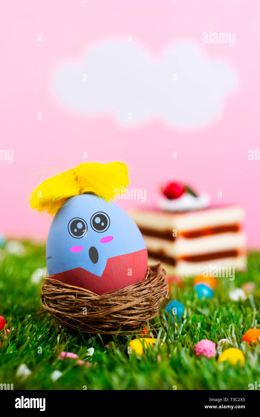 closeup of a handmade easter egg, with cute and funny face, on the grass with a pink sky with white clouds and a piece of cake in the background - Stock Image