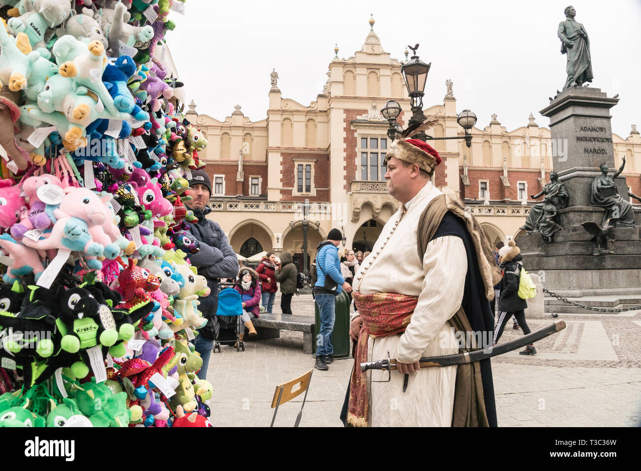 Krakow, Poland - March 22, 2019 - souvenirs, artist in traditional costume and Adam Mickiewicz Monument on Main Market Square Stock Photo
