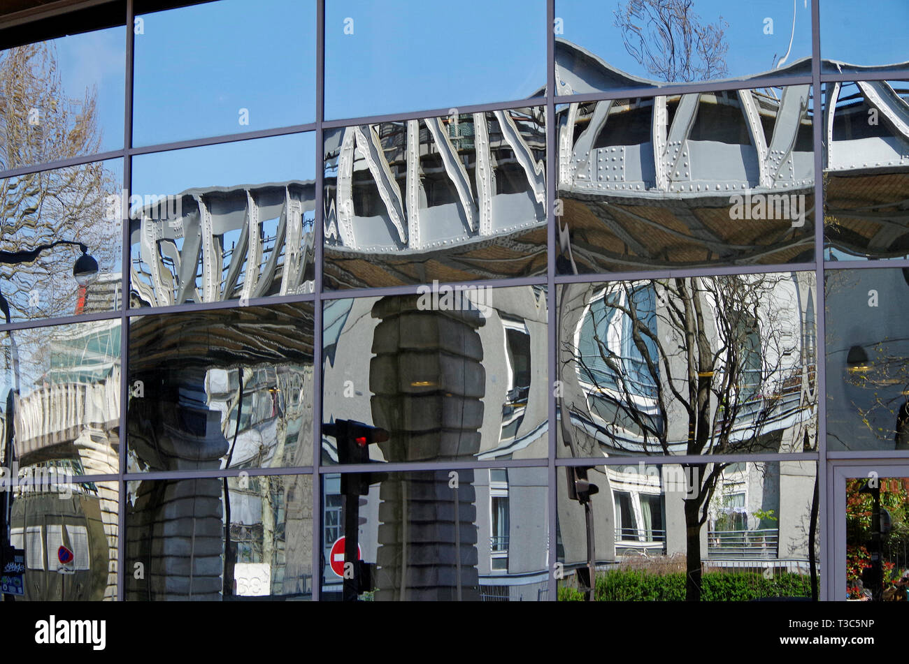 Distorted reflections of iron viaduct with iron & stone columns of the elevated Metro Line 6 seen in a mirror-glazed office building beside the tracks - Stock Image