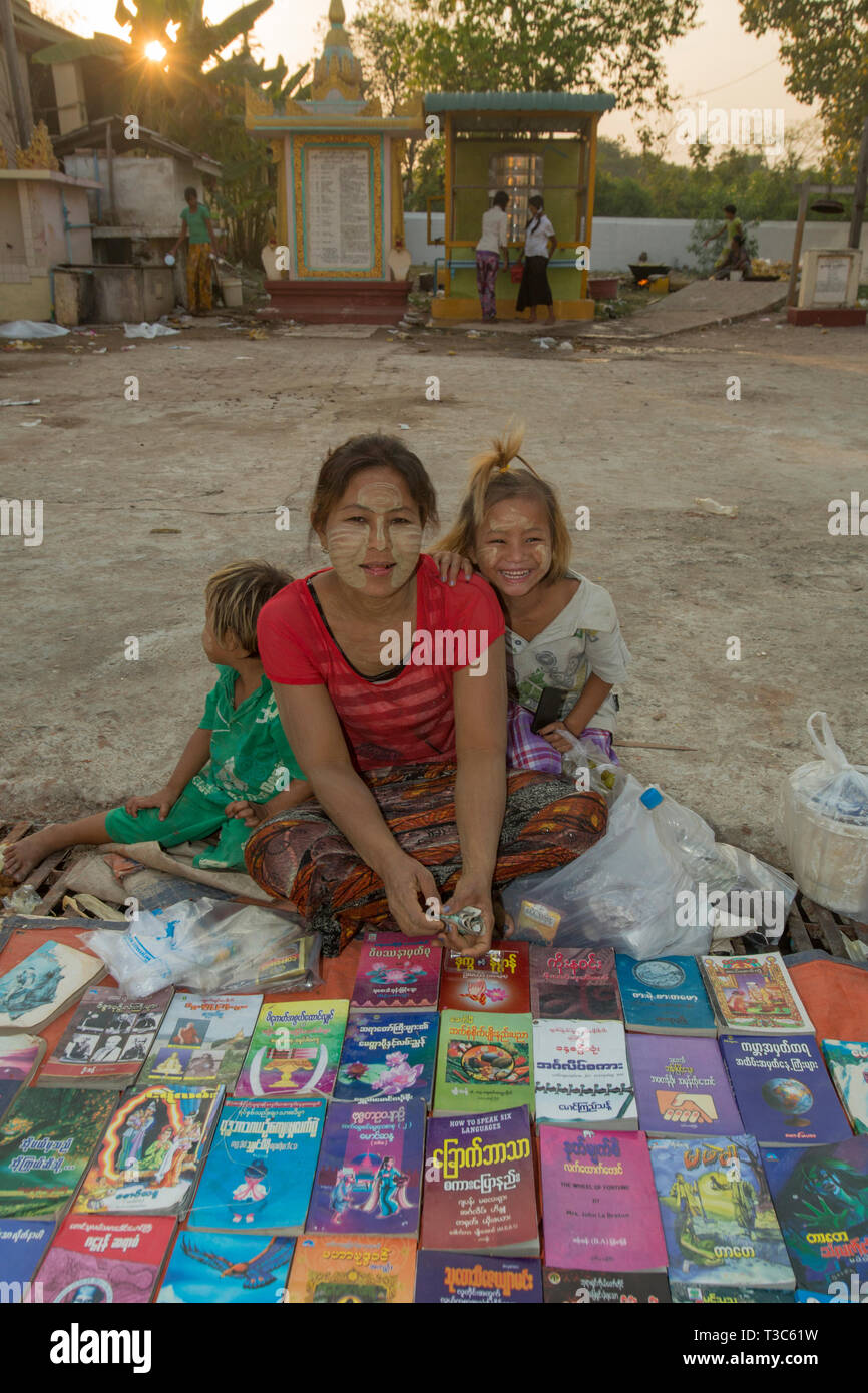 Book seller and her children at the Vesak full moon festival to celebrate the birthday of Lord Buddha at Shwe Yin Maw Pagoda, near Thazi, Myanmar (Bur - Stock Image