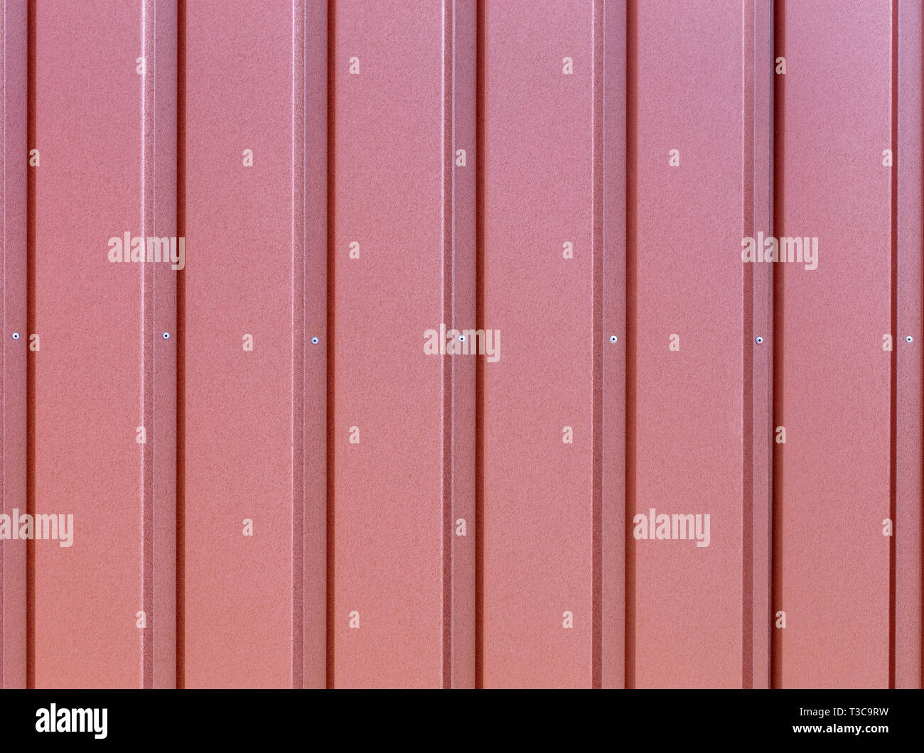 Reddish-brown metal fence made of corrugated steel sheet with vertical guides and metal rivets in the middle. Corrugated reddish-brown iron sheet back - Stock Image