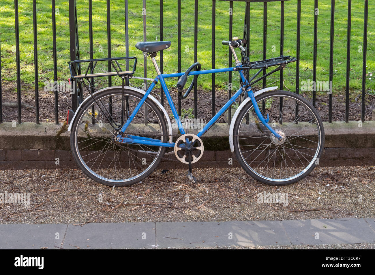 Old blue bicycle leaning against railings in New Walk, Leicester, UK - Stock Image