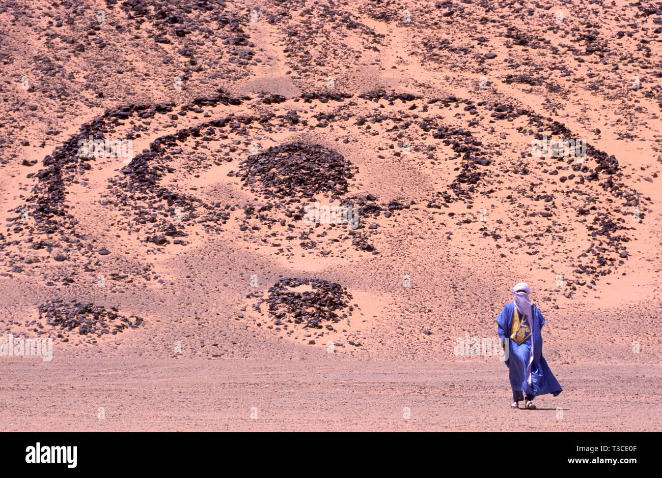 Tuareg man in a traditional costume with a 5000 year old grave in the background in the Sahara in Algeria - Stock Image