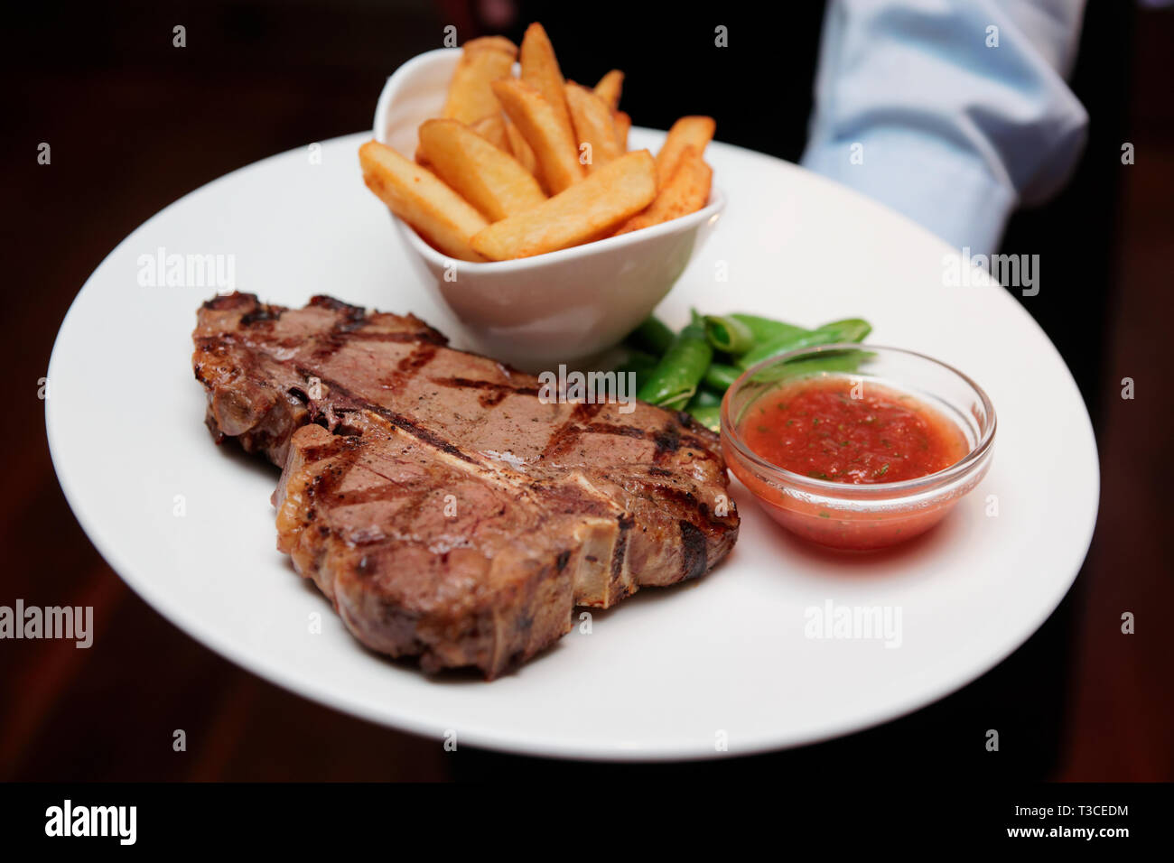 Waiter offering T-bone steak with french fries and hot sauce - Stock Image