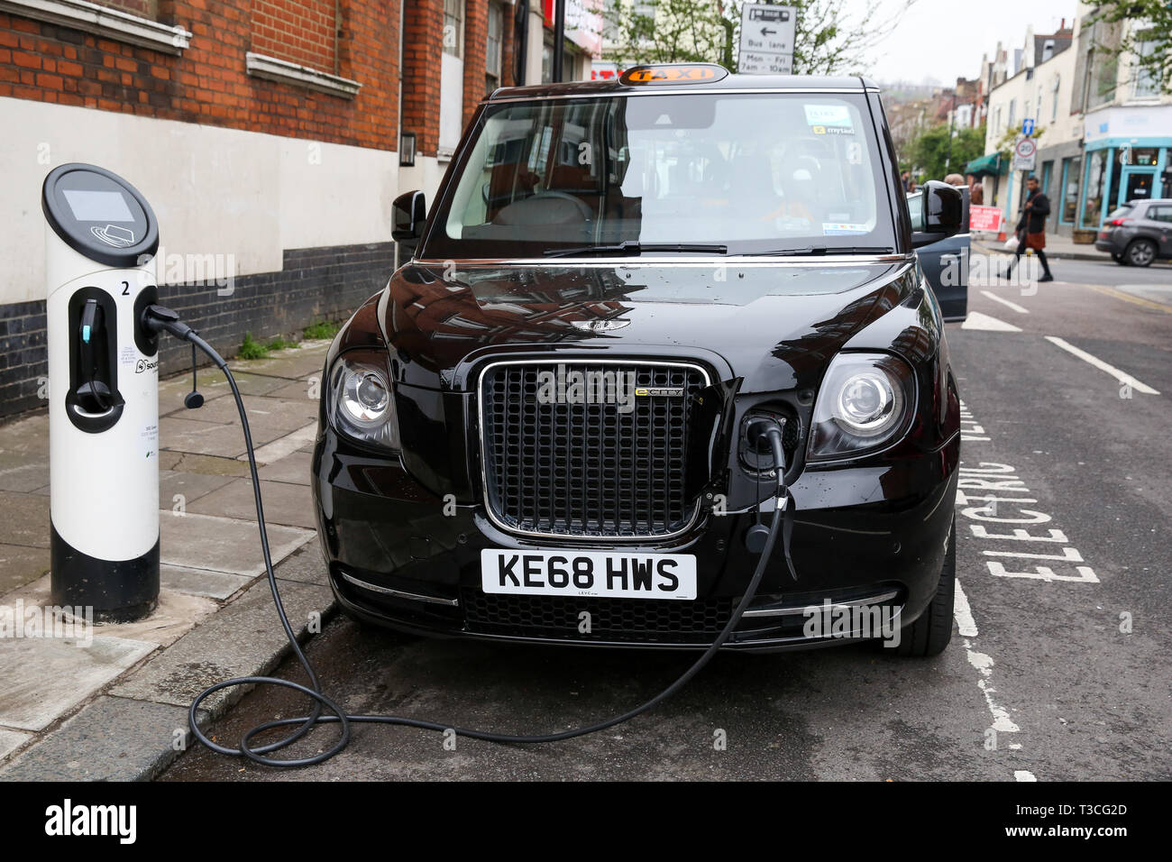 A black London taxi is seen using the electric car charging point in London.   To help improve air quality, an Ultra-Low Emission Zone (ULEZ) which came into force on Monday 8 April 2019, now operates 24 hours a day, 7 days a week, within the same area of central London as the Congestion Charge.  Drivers must meet the ULEZ emissions standards or have to pay a daily charge, in addition to Congestion Charge to drive within the zone, Black cabs are exempted from Ultra Low Emission Zone charge. - Stock Image