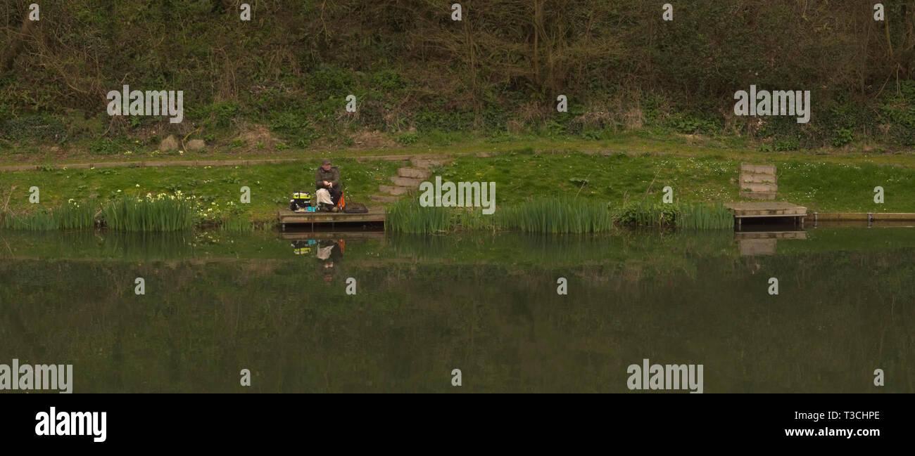 Freshwater angler on pond bank - Stock Image