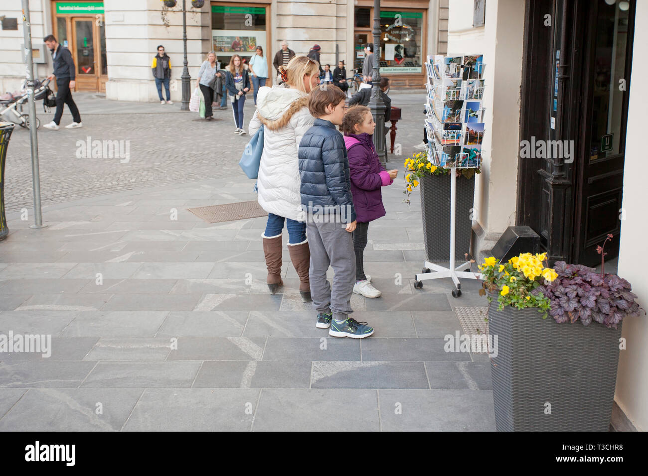 Tourists in Slovenia's capital browsing postcards - Stock Image