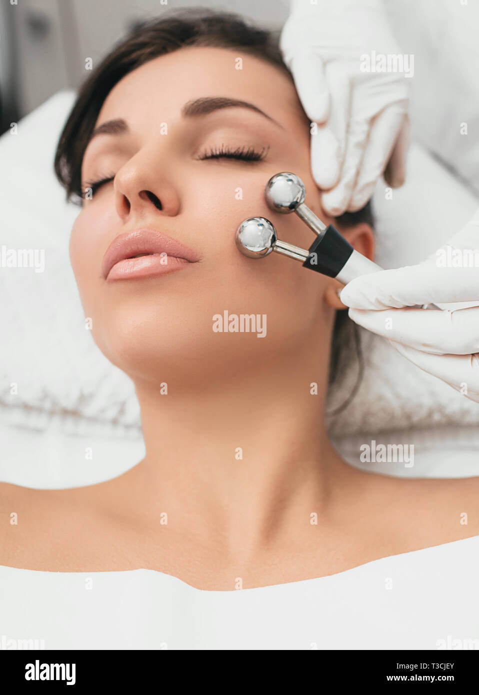 Beautiful woman receiving facial microcurrent procedure for lifting face. Facial rejuvenation and facelift with microcurrent therapy Stock Photo