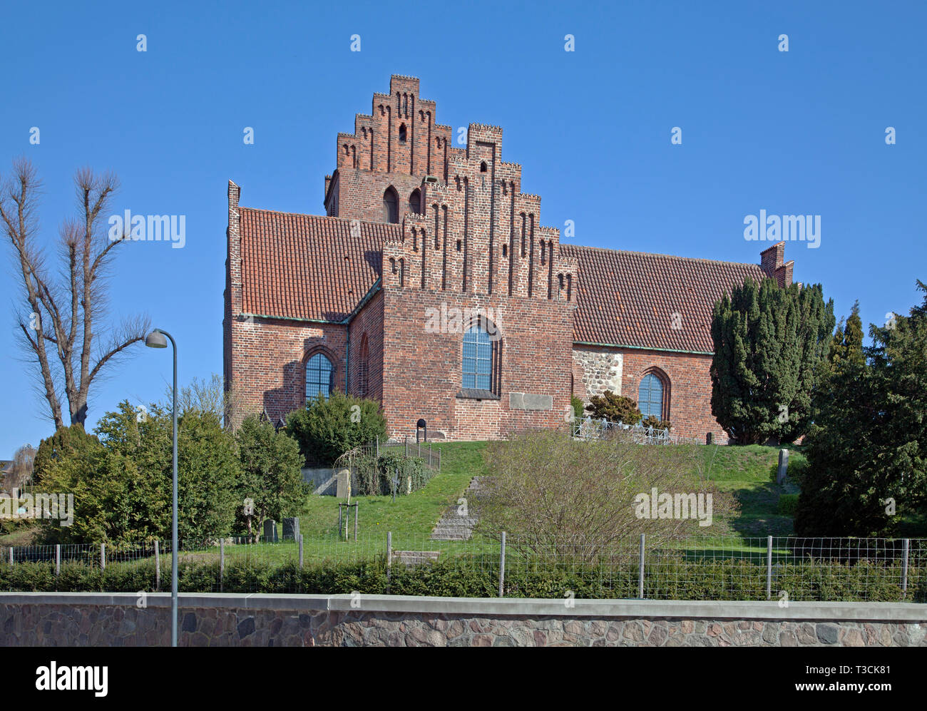 Lyngby Church in Romanesque style orig. from mid 12th century. Lengthened in Late Gothic era.standing high on hill seen from Lyngby main street. - Stock Image