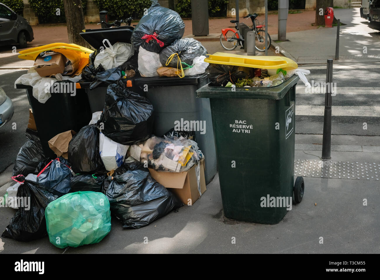 Full bins on the sidewalks of the city of Lyon during the garbage workers' strike - Stock Image