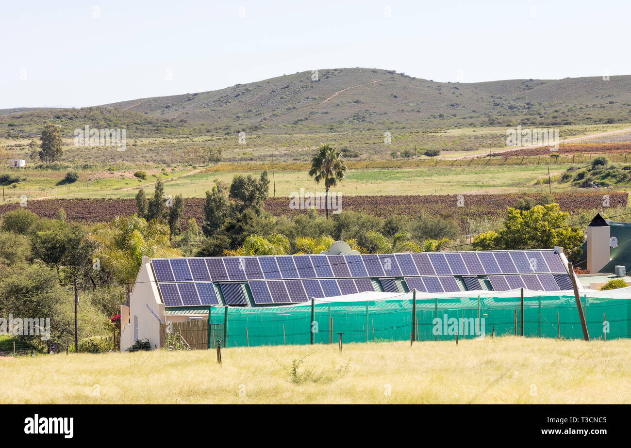 Environmentally friendly farmhouse with  rooftop solar photovoltaic panels providing renewable energy and electricty  in a rural landscape, South Afri - Stock Image