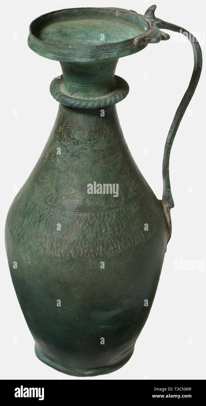 A Roman bronze ewer with silver inlays, 2nd - 4th century A.D. Bronze with greenish patina. Slender, slightly bellied ewer. Slender cordoned neck and widely flared rim. Narrow handle terminating in two animal heads. The shoulder surrounded by an engraved leaf frieze, surmounted by the punched and silver inlaid portrayal of two birds. Cleaned archaeological find. Restorations to the neck, rim, foot, and the right side. Height 30.5 cm. historic, historical, ancient world, ancient world, ancient times, object, objects, stills, clipping, cut out, cut, Additional-Rights-Clearance-Info-Not-Available Stock Photo