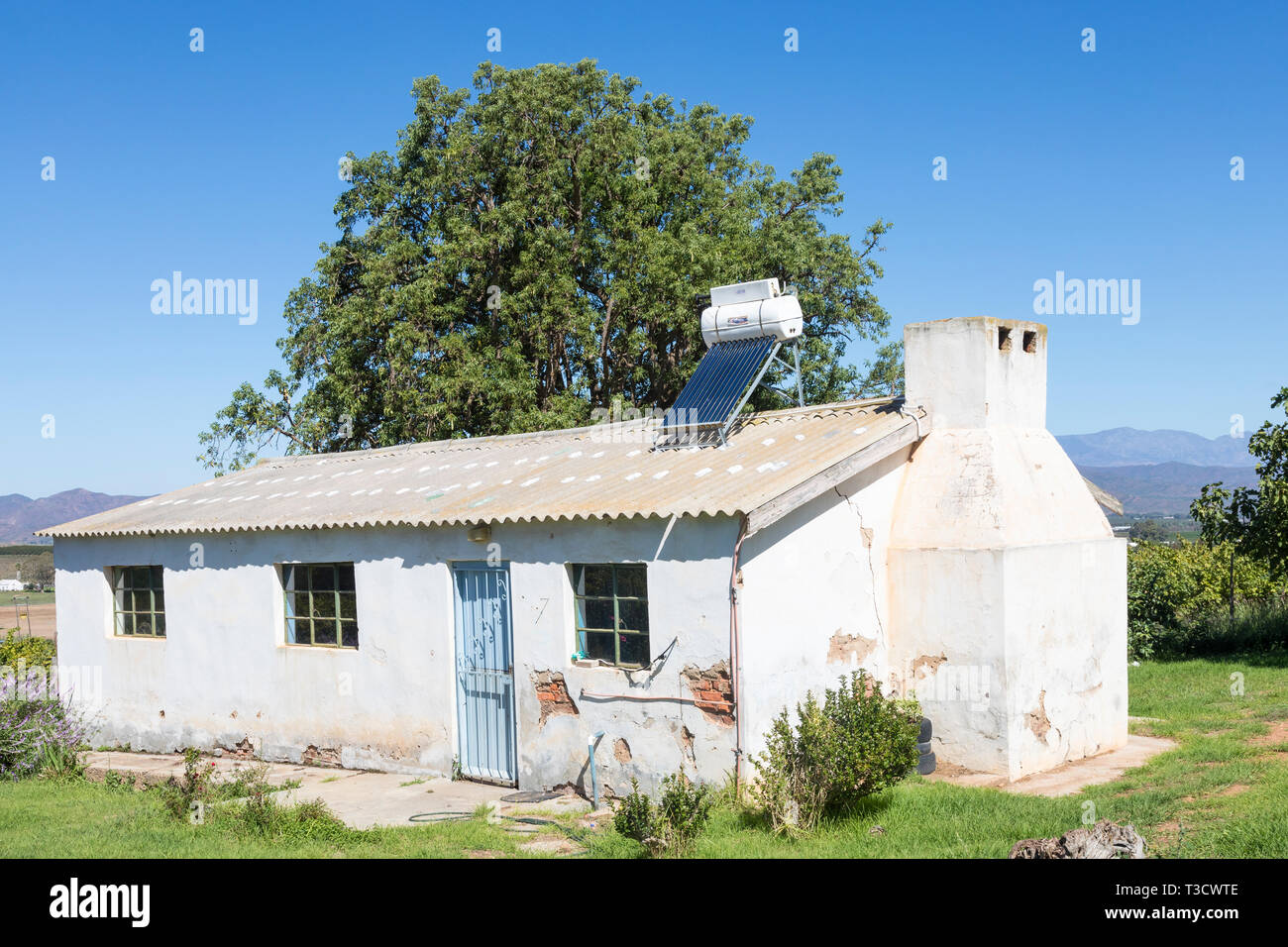 Farmworkers cottage with small roof mounted solar hot water geyser and photovoltaic panel, natural resource, renewable, sustainable, power, energy, he - Stock Image