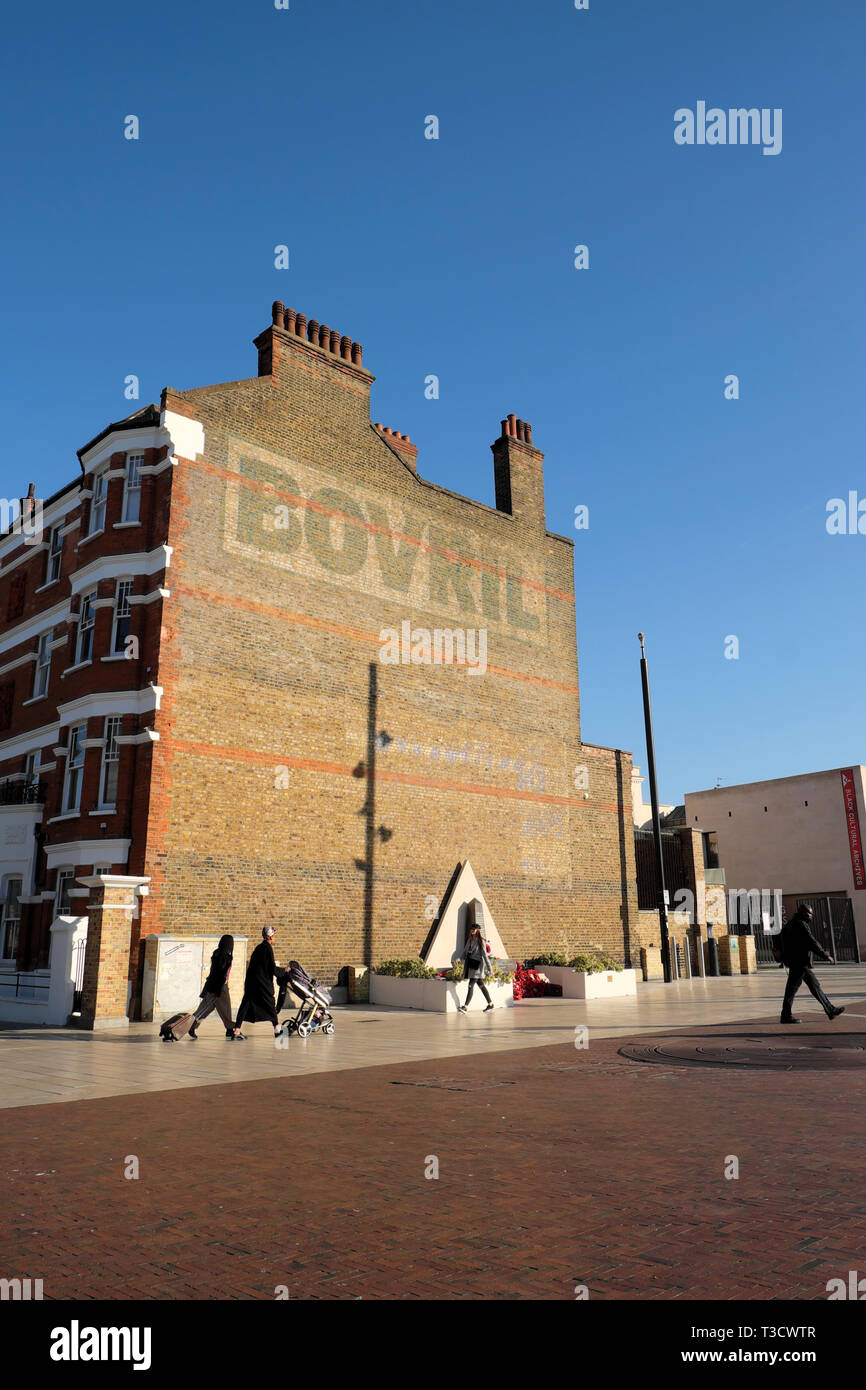 Vertical view of people walking pedestrians in Windrush Square and the Bovril building with blue sky in Brixton South London England UK  KATHY DEWITT - Stock Image