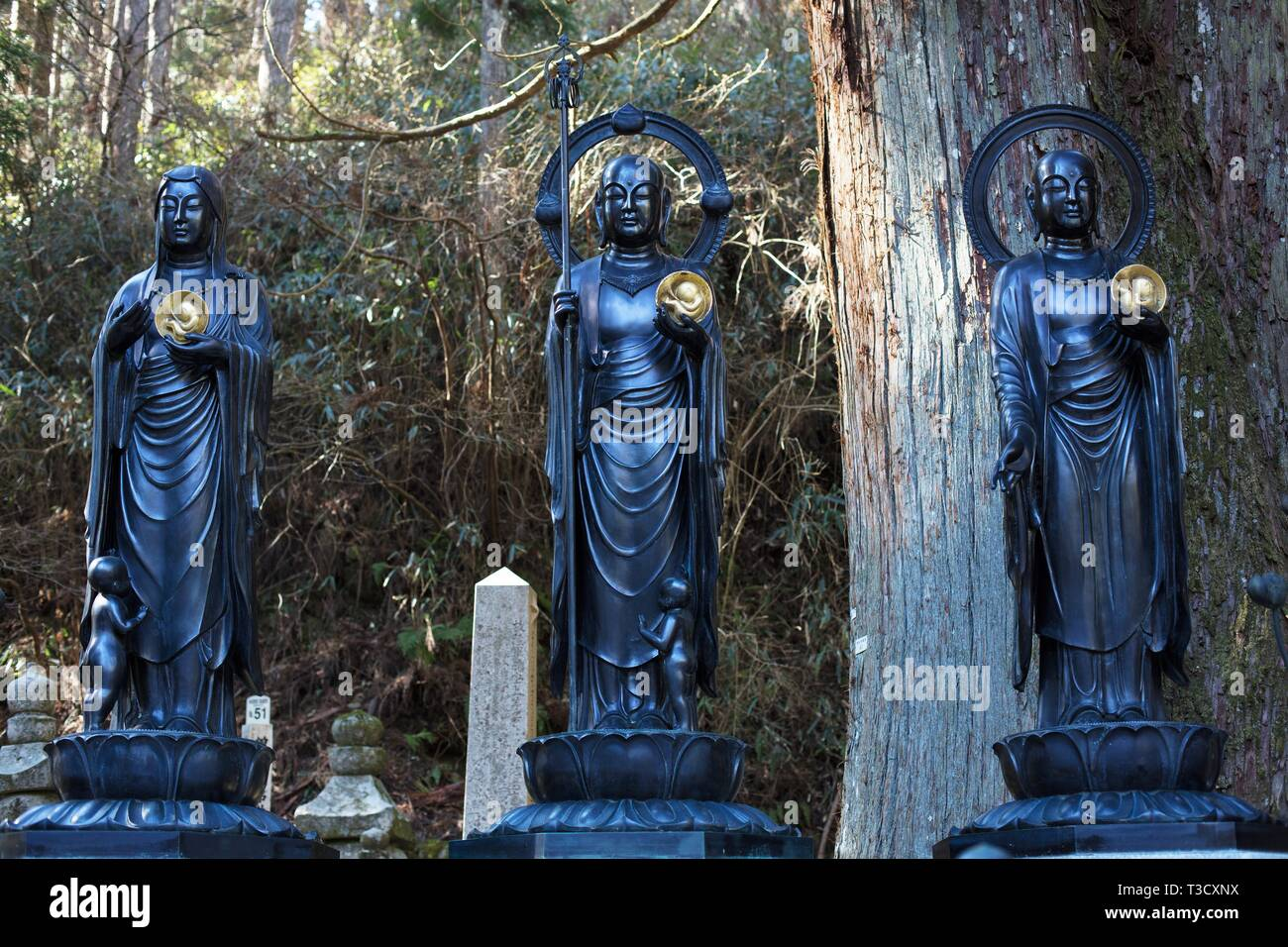 Three black robed statues holding golden fetuses in Okunoin cemetery in Koyasan, Japan. - Stock Image