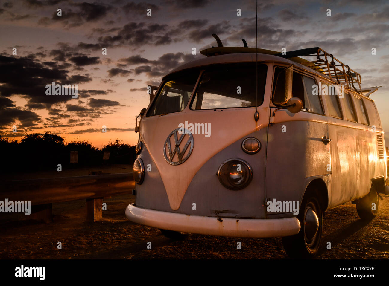 Vintage Volkswagon VW Microbus with rooftop rack for surfboards, parked along cliffs at Sunset Cliffs, San Diego, CA, USA Stock Photo