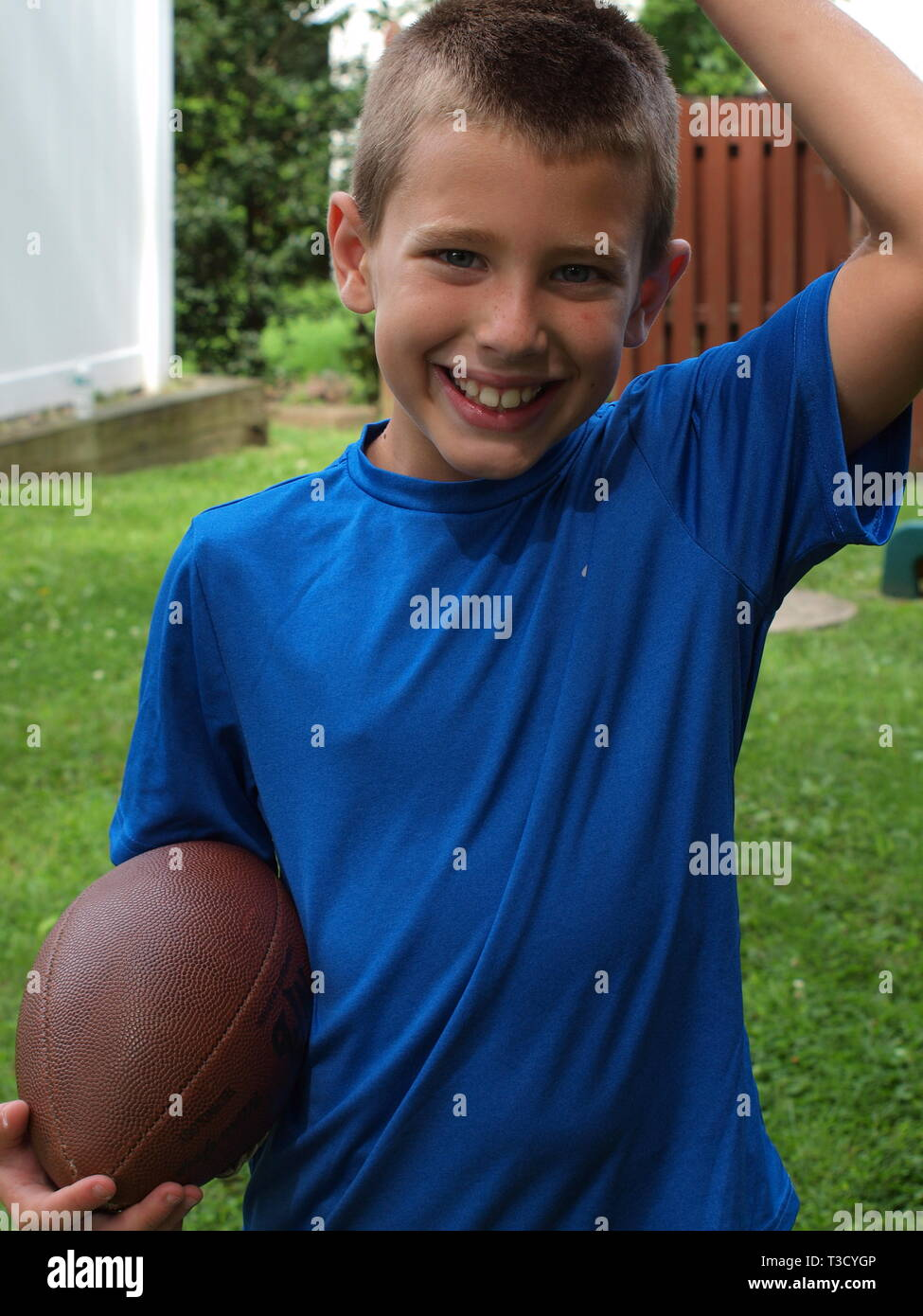 Smiling blue eyed boy in blue shirt and carrying a football ready to play. - Stock Image