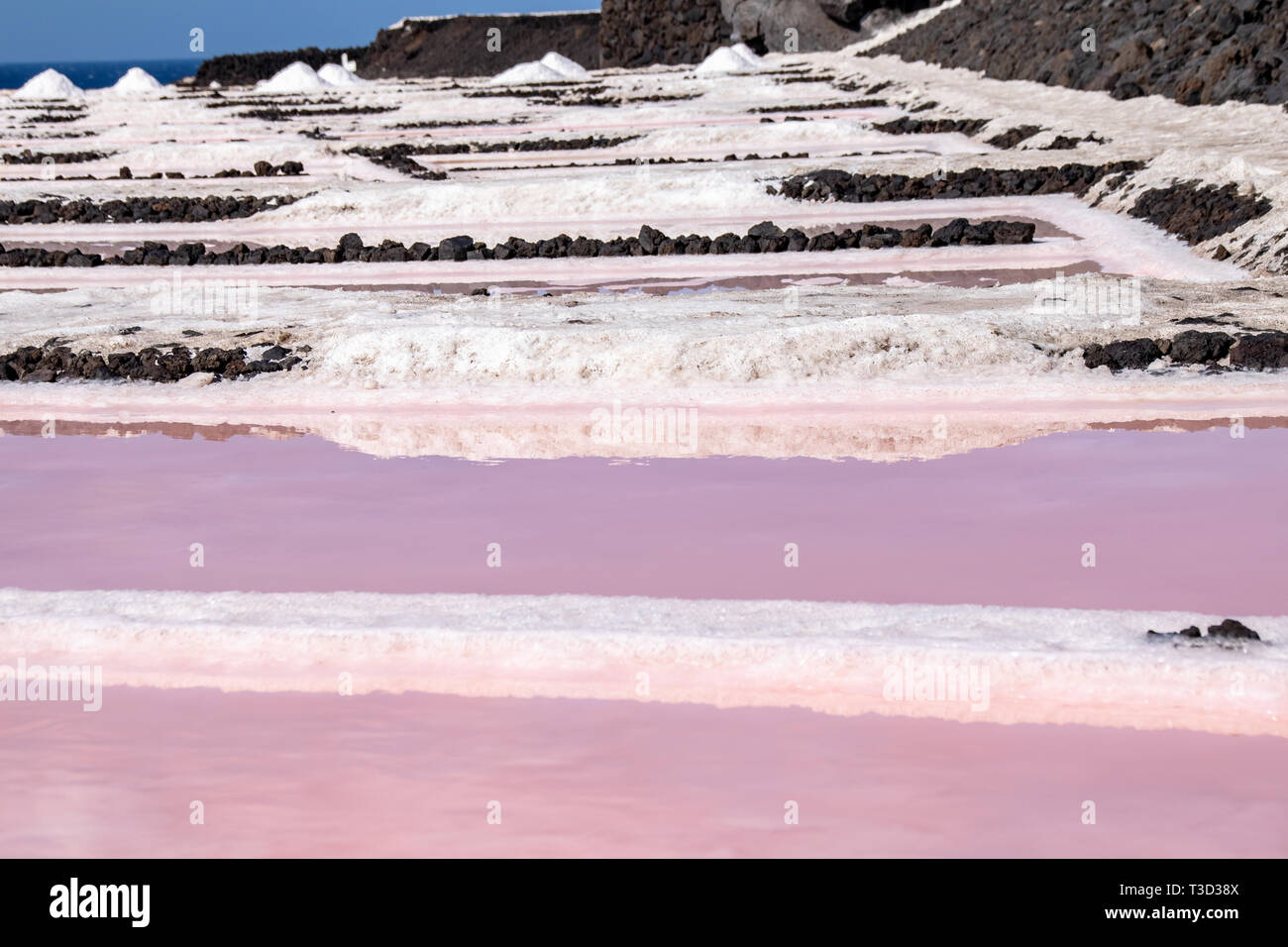 Reflections of salt evaportations in the pink colors of saline water during the production process in the salt fields of Fuencaliente, La Palma Island Stock Photo