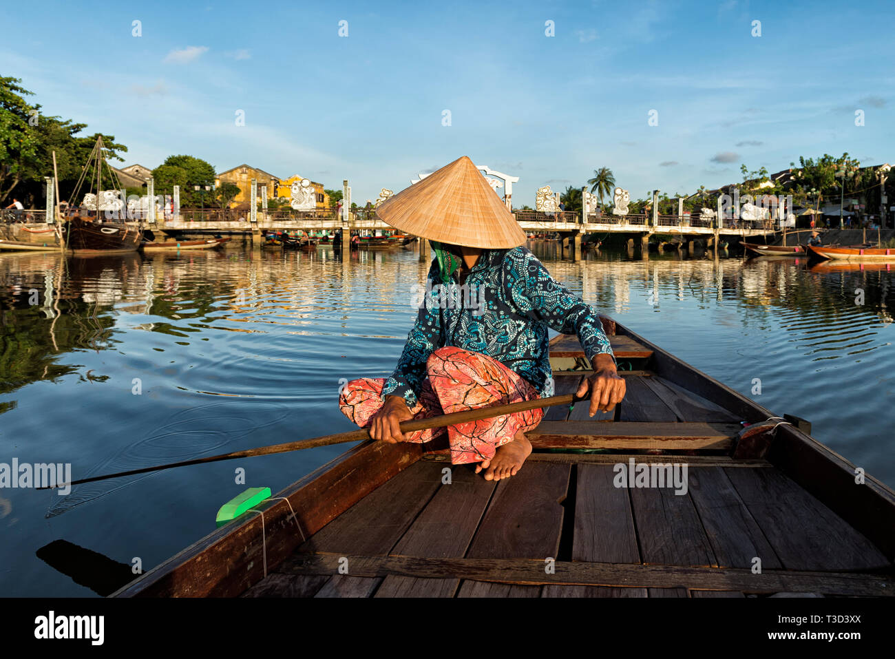 Vietnamese woman with colourful clothes on her boat with Cau An Hoi Bridge in the background - Stock Image