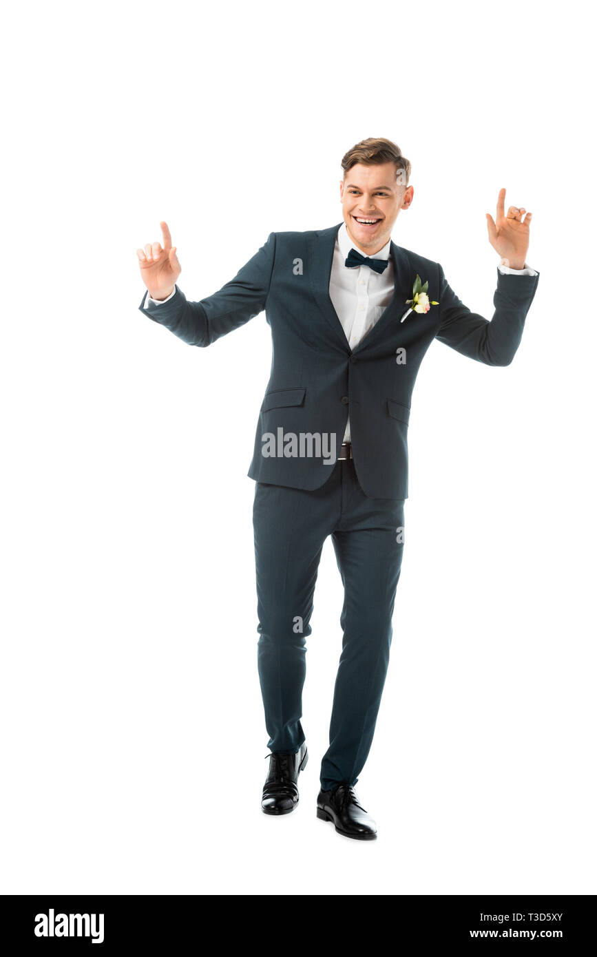 cheerful dancing groom in black suit isolated on white - Stock Image