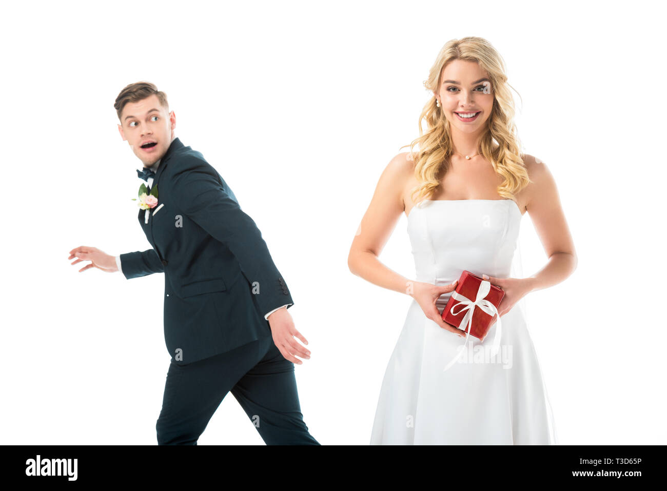 happy beautiful bride holding gift box, while tricky groom imitating running away isolated on white Stock Photo