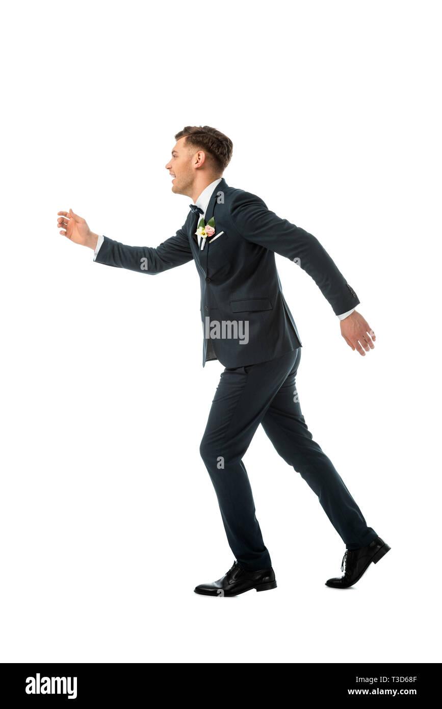 cunning cheerful bridegroom imitating running away isolated on white Stock Photo
