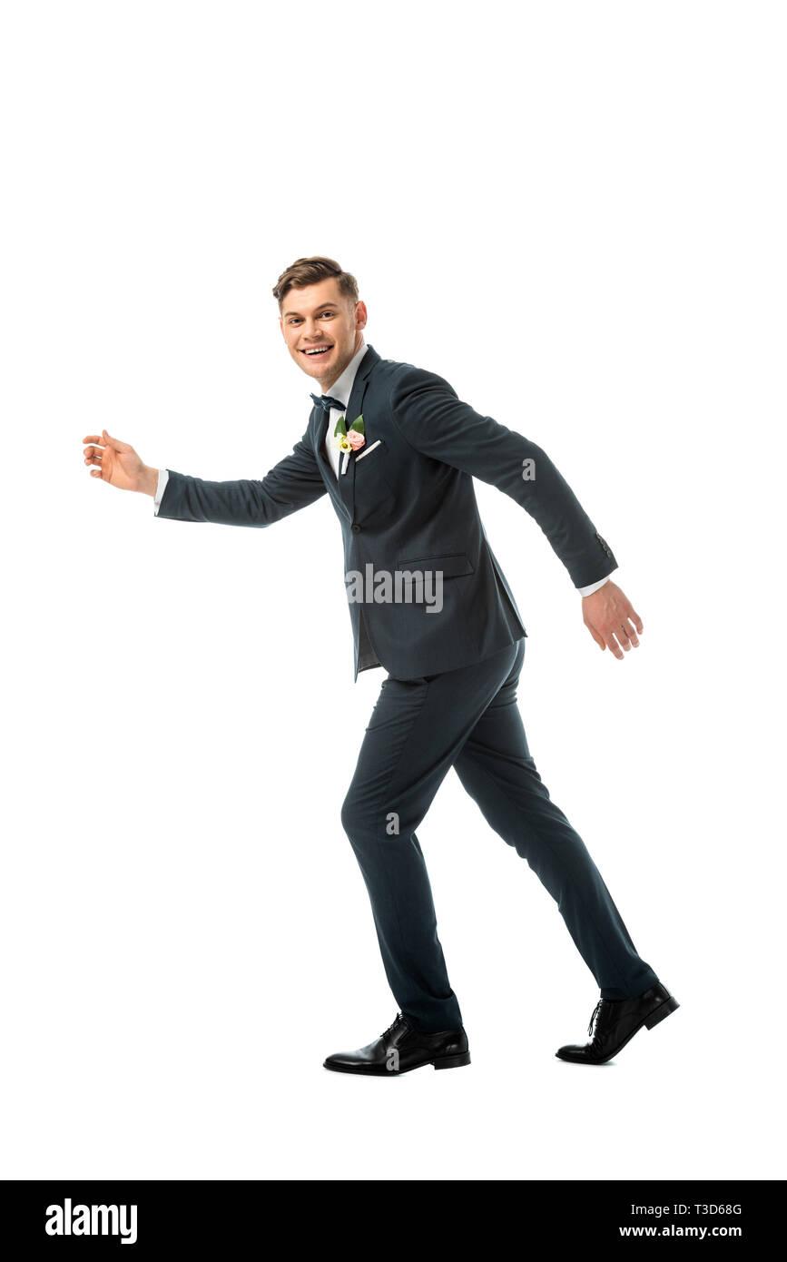 tricky cheerful bridegroom imitating running away isolated on white - Stock Image