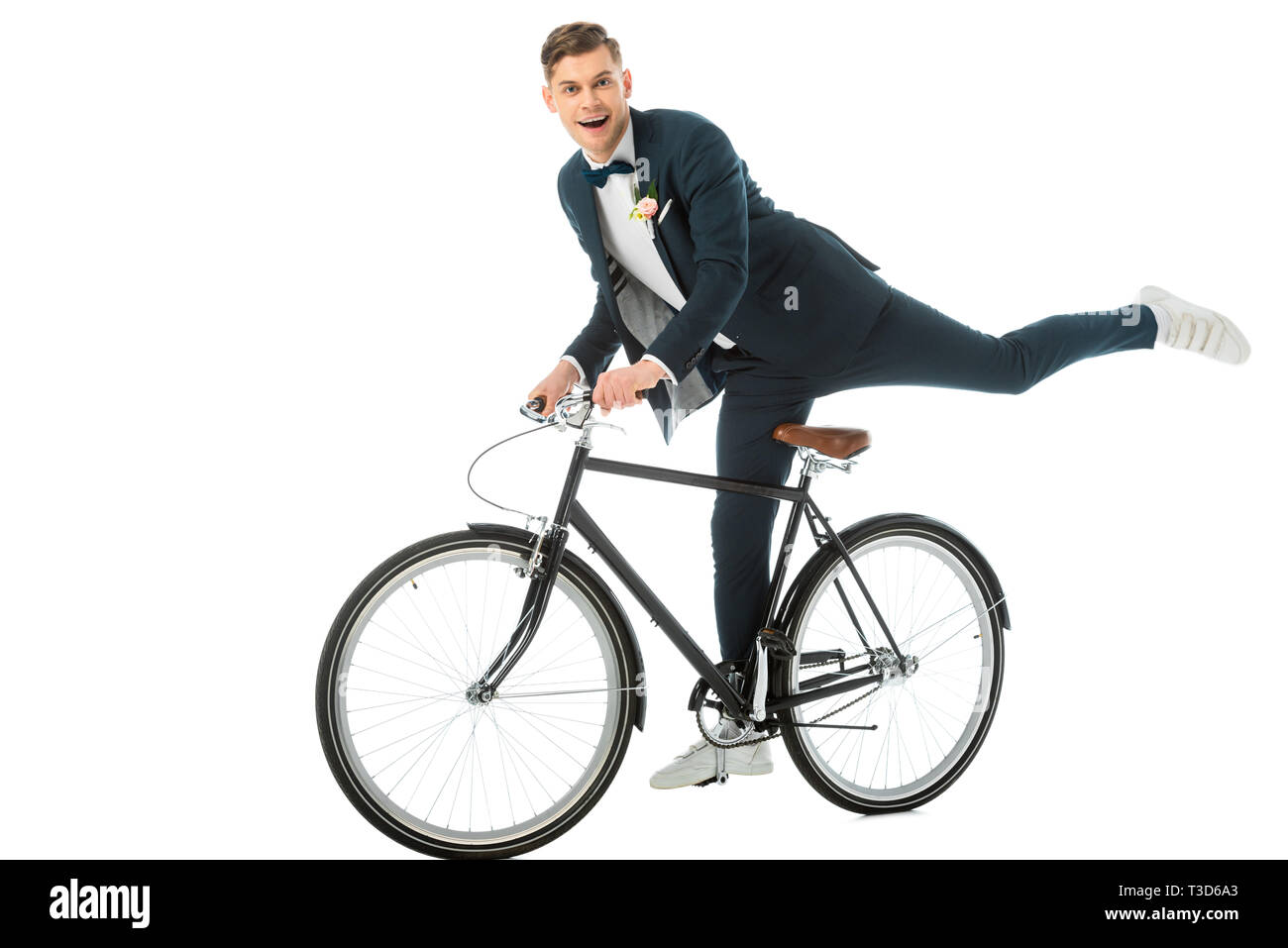 cheerful groom in elegant suit making stunts on bike isolated on white - Stock Image