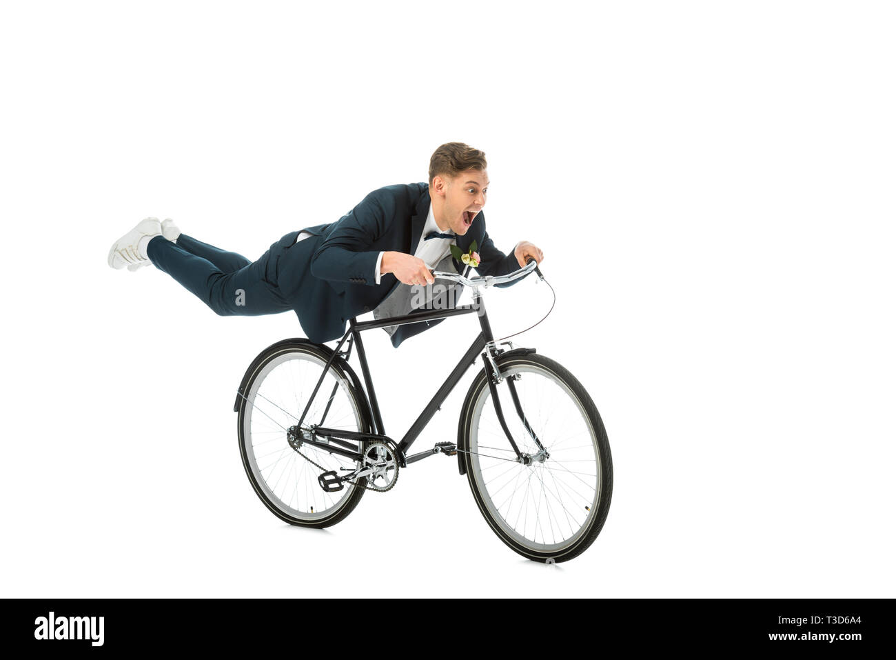 excited groom in elegant suit making stunts on bike isolated on white - Stock Image