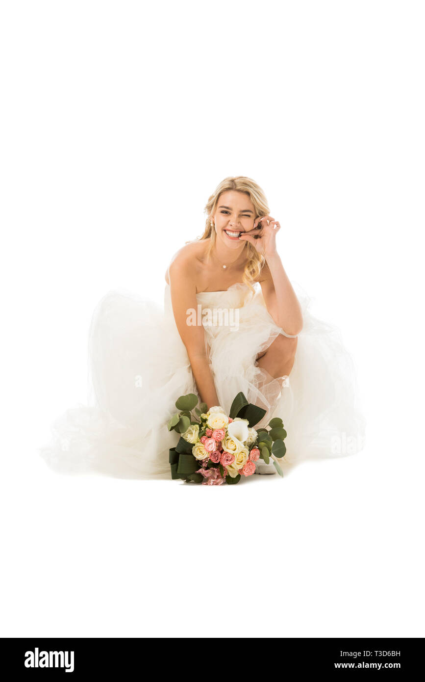 tricky cheerful bride funny grimacing and holding wedding bouquet isolated on white - Stock Image