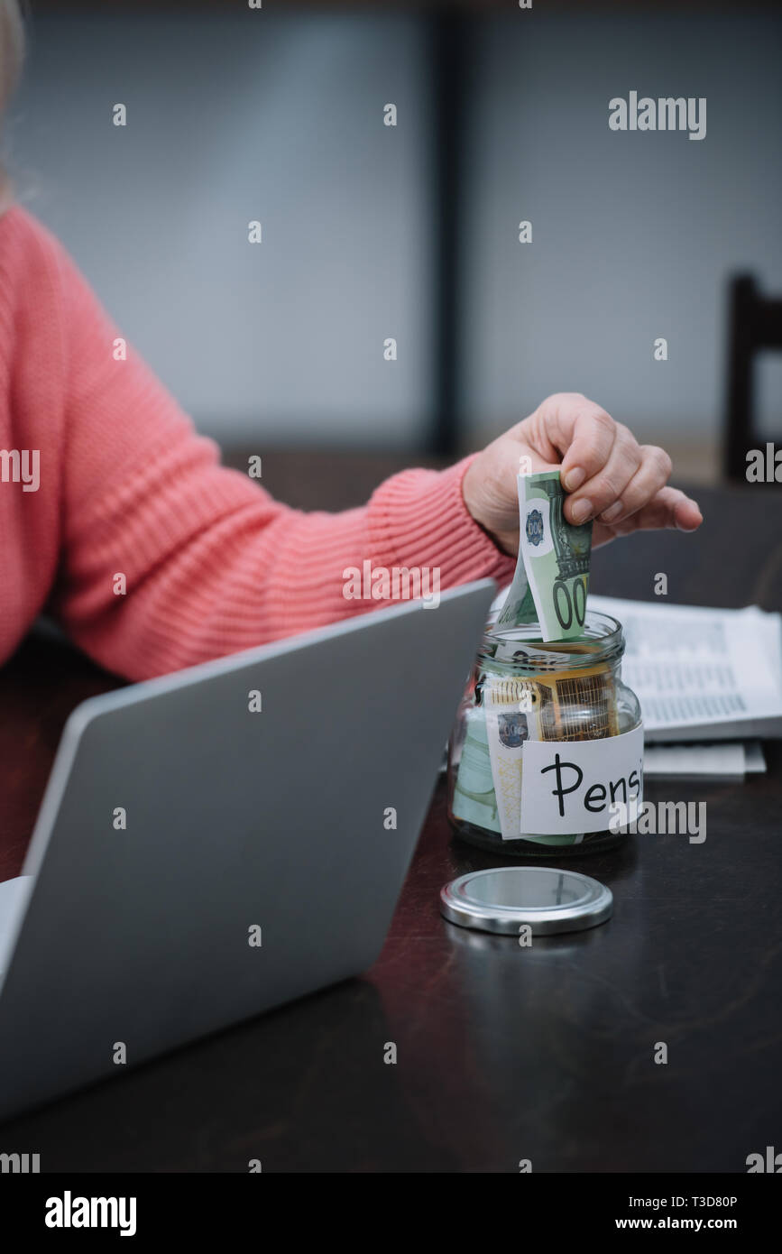 cropped view of senior woman sitting at table with laptop while putting money in glass jar with 'pension' word Stock Photo