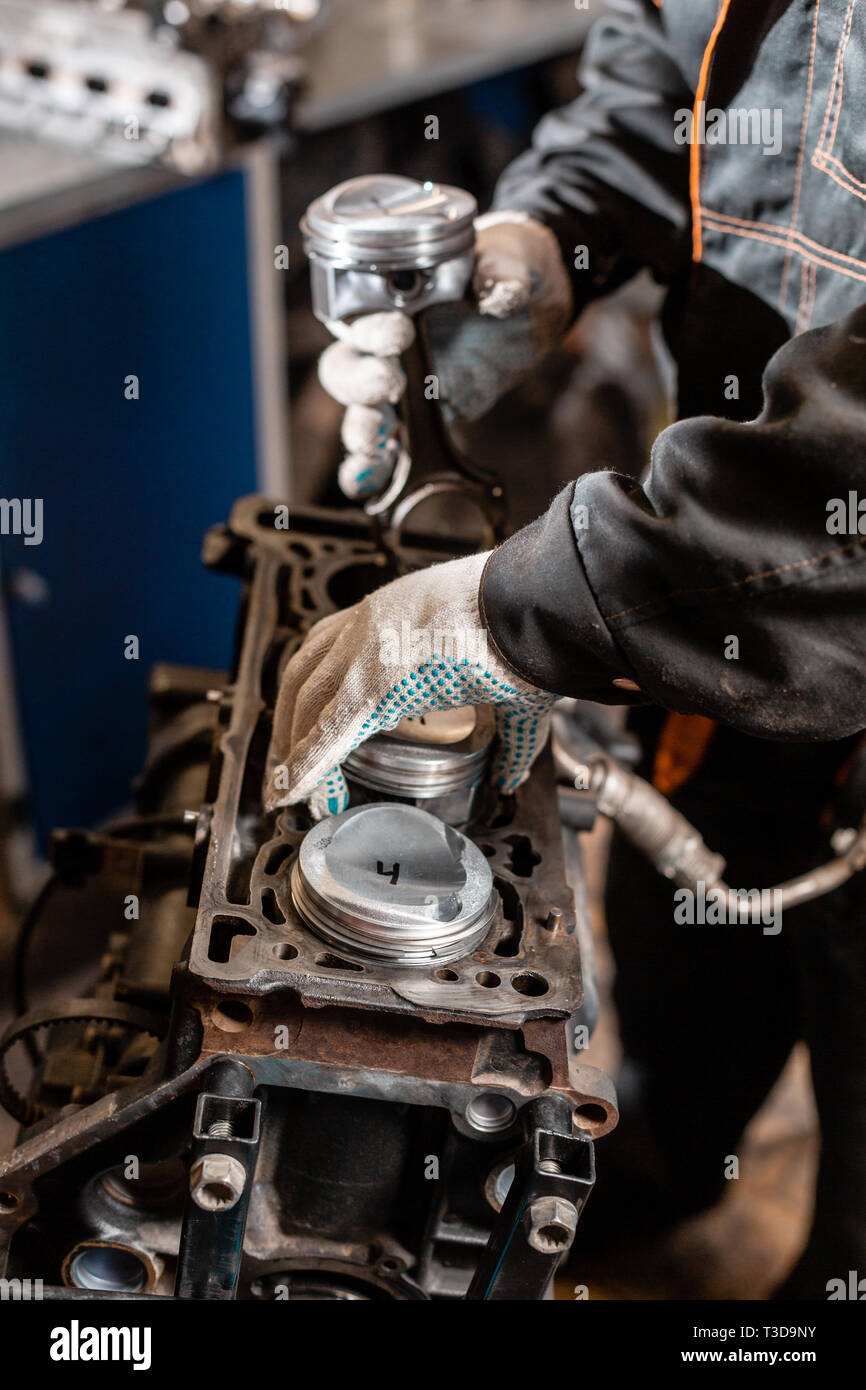 close-up car mechanic holding a new piston for the engine, overhaul   engine  on a repair stand with piston and connecting rod of automotive technology