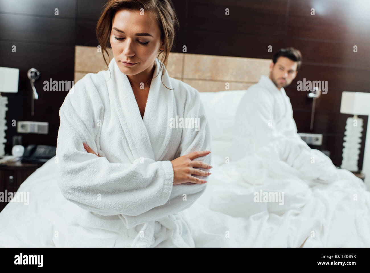 selective focus of beautiful woman sitting with crossed arms near boyfriend after quarrel - Stock Image