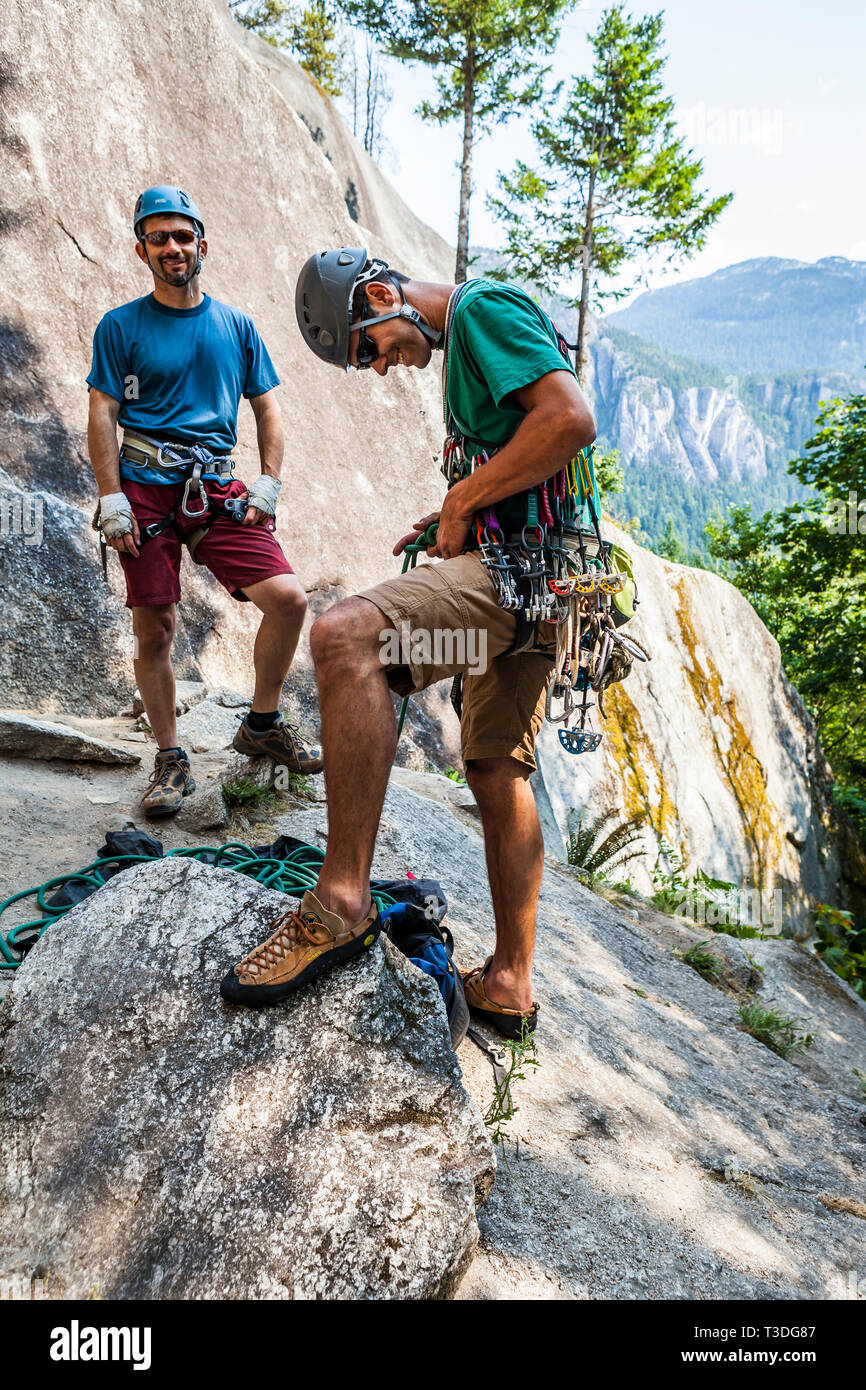 A man tying into a climbing rope while getting ready to lead a rock climb while his partner stands by ready to belay. The Little Smoke Bluffs, Squamis - Stock Image