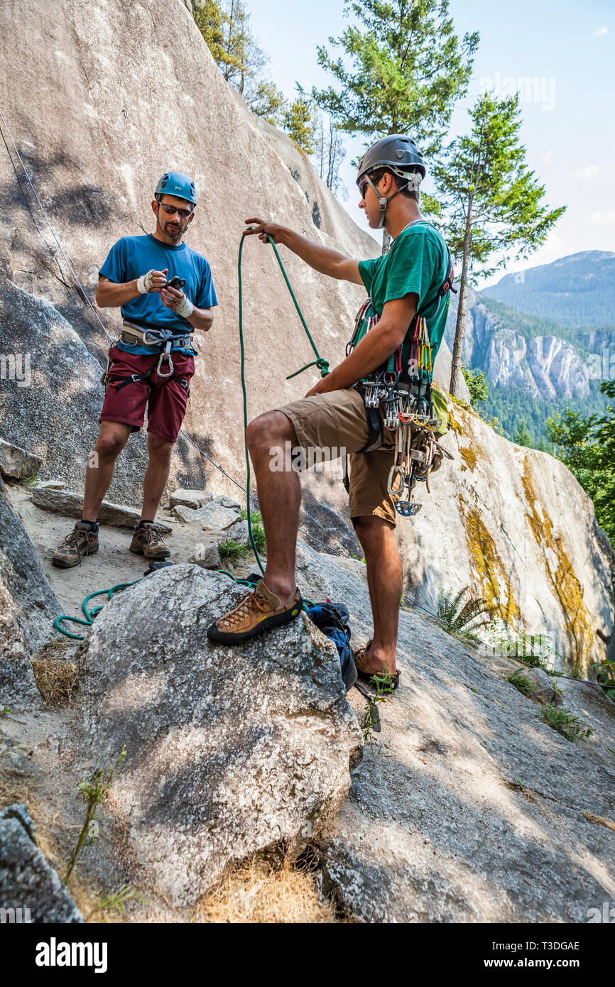 A man handing the climbing rope to his climbing partner before starting up a climbing route. The Little Smoke Bluffs, Squamish, BC, Canada. - Stock Image
