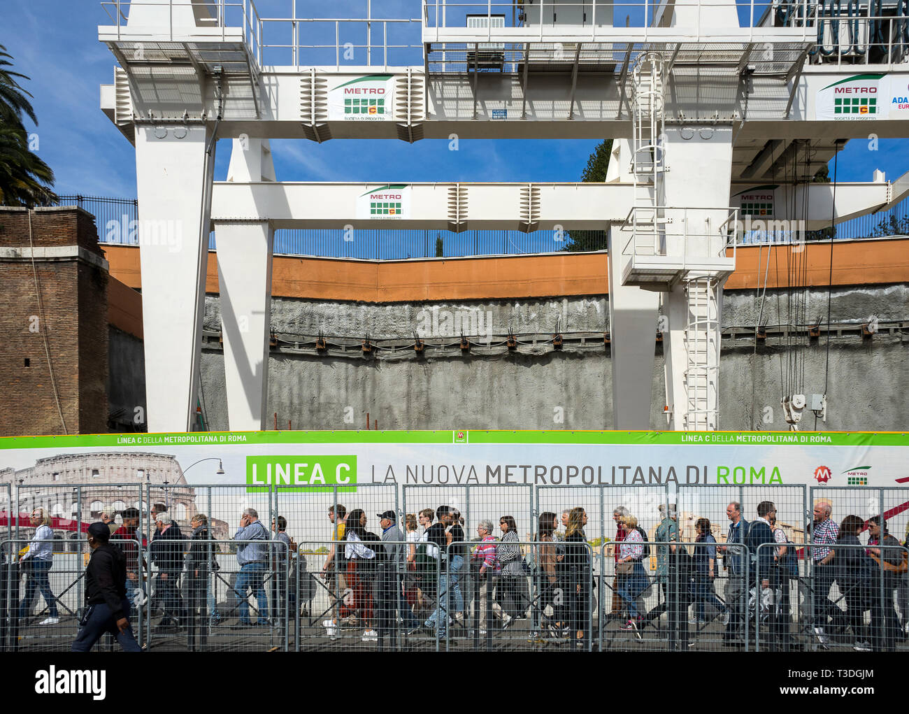 Colosseum, Rome, Italy 04/06/2019: new metro line c building, Fori Imperiali Station. In close-up people strolling, construction site with cranes in t - Stock Image