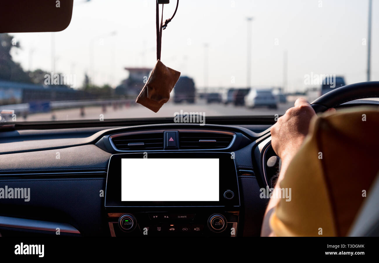 Mock up of Isolated blank screen monitor in car for your advertising. The man behind the wheel, driving in traffic with car radio mockup. Stock Photo