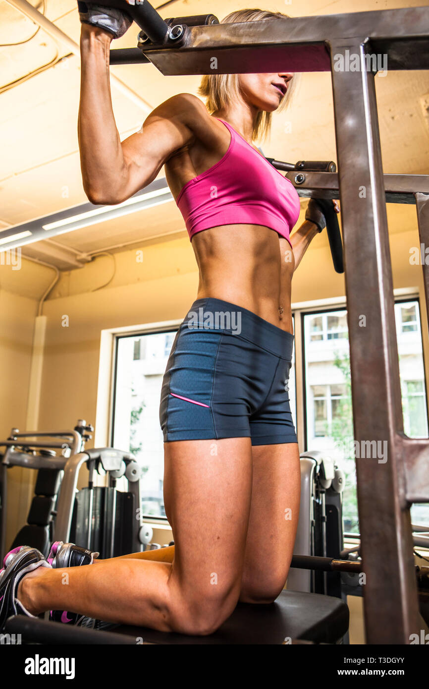 Physically fit woman on a pullup machine in a healthclub. - Stock Image