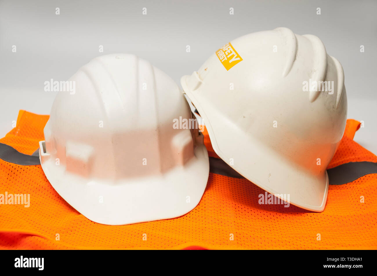 Two used hard hats and an orange vest. - Stock Image