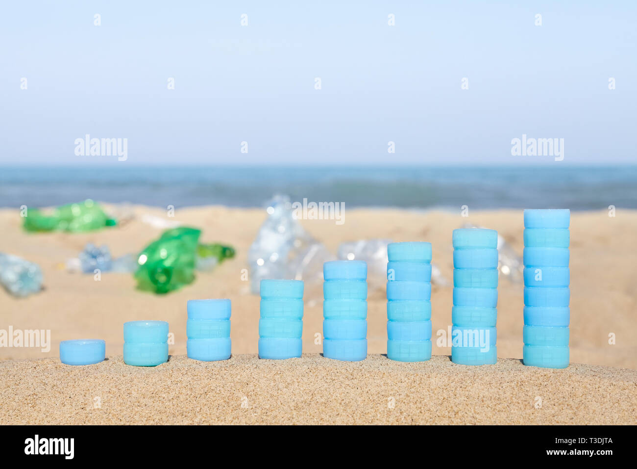 Chart made of plastic bottles caps on sand showing the increase in single use plastic products found on European beaches. - Stock Image