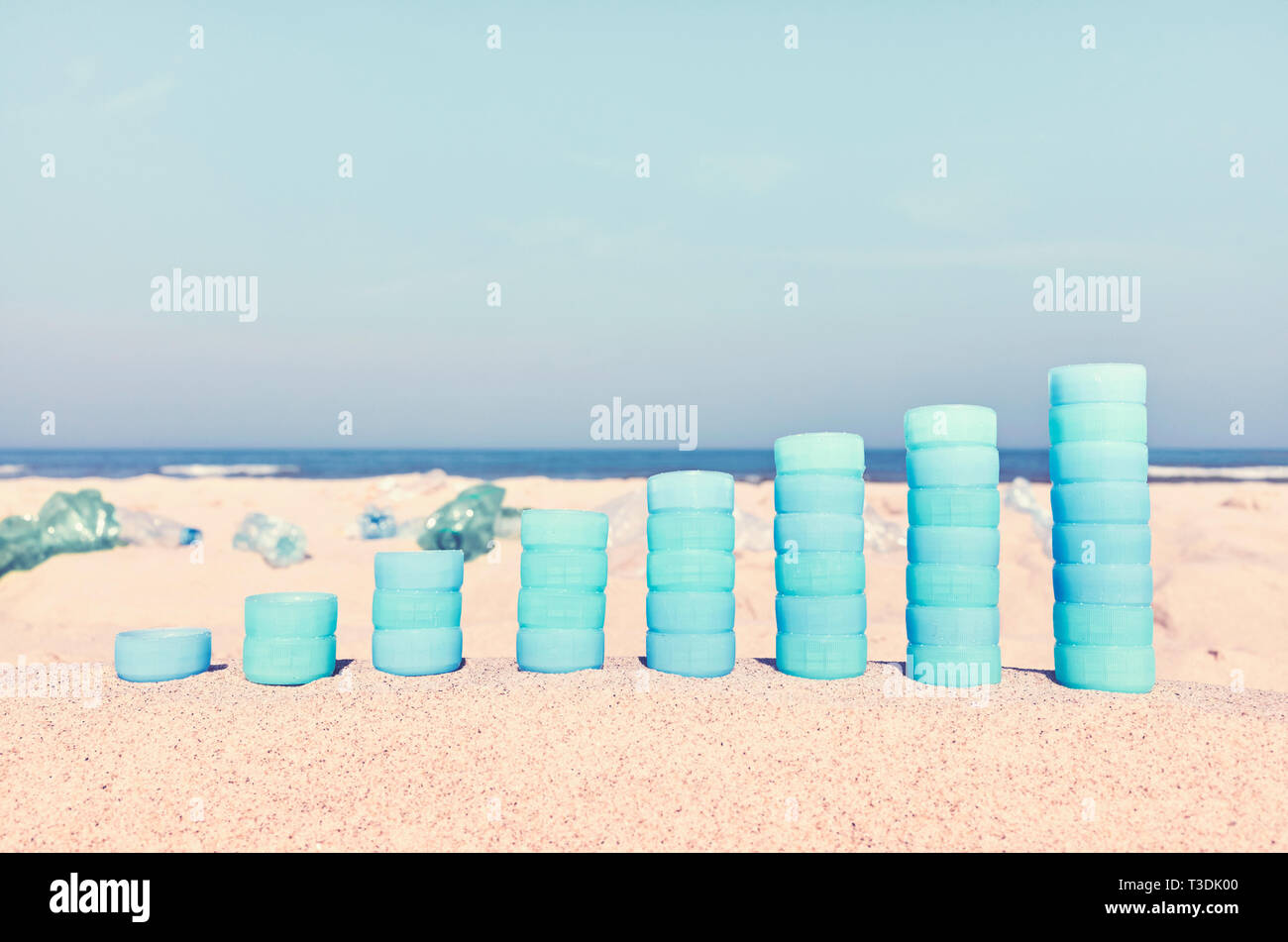 Chart made of plastic bottles caps on sand showing the increase in use of plastic products, color toned picture, selective focus. - Stock Image