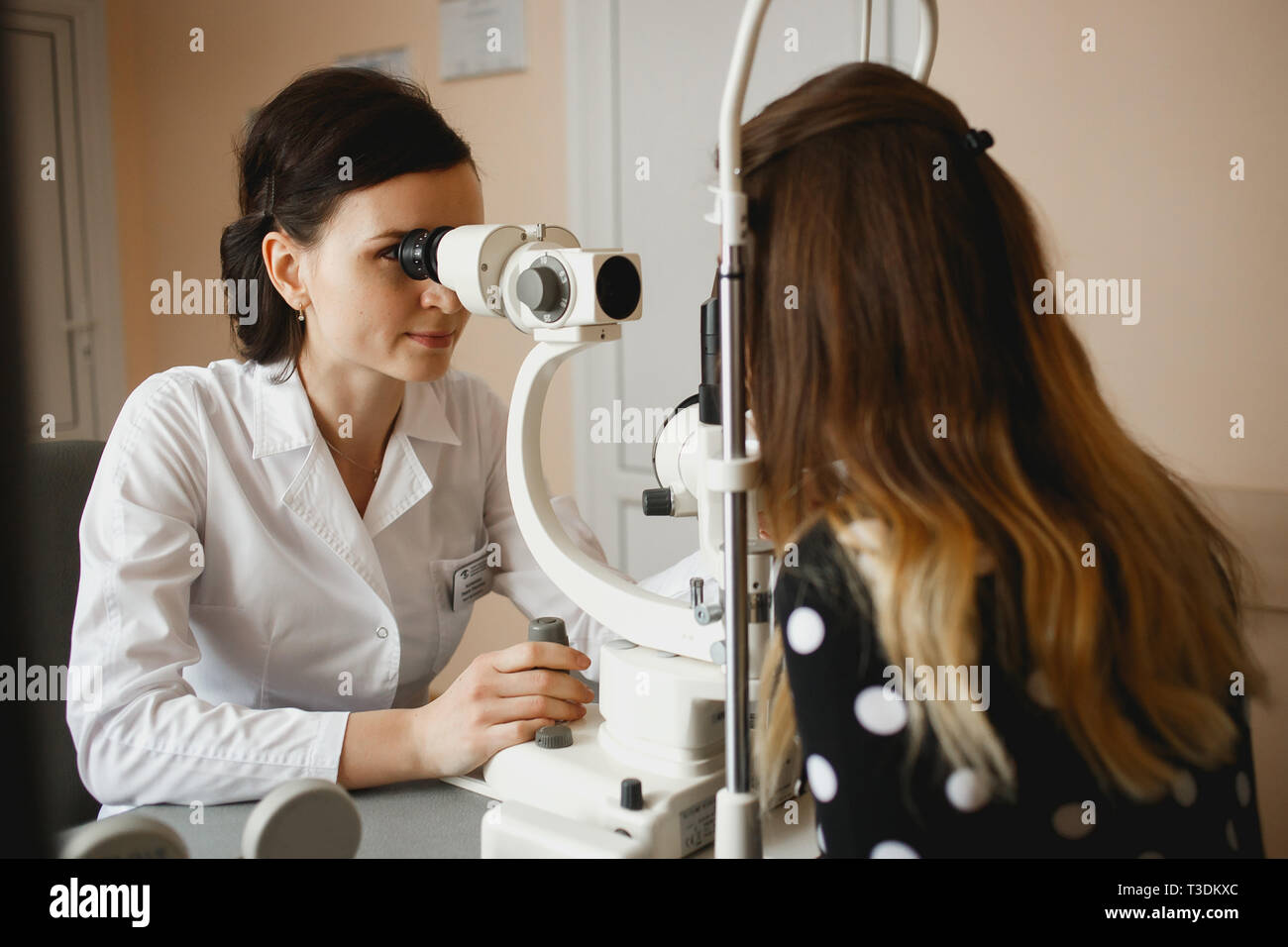 Attractive female doctor ophthalmologist is checking the eye vision of young woman in modern clinic. Doctor and patient in ophthalmology clinic. - Stock Image