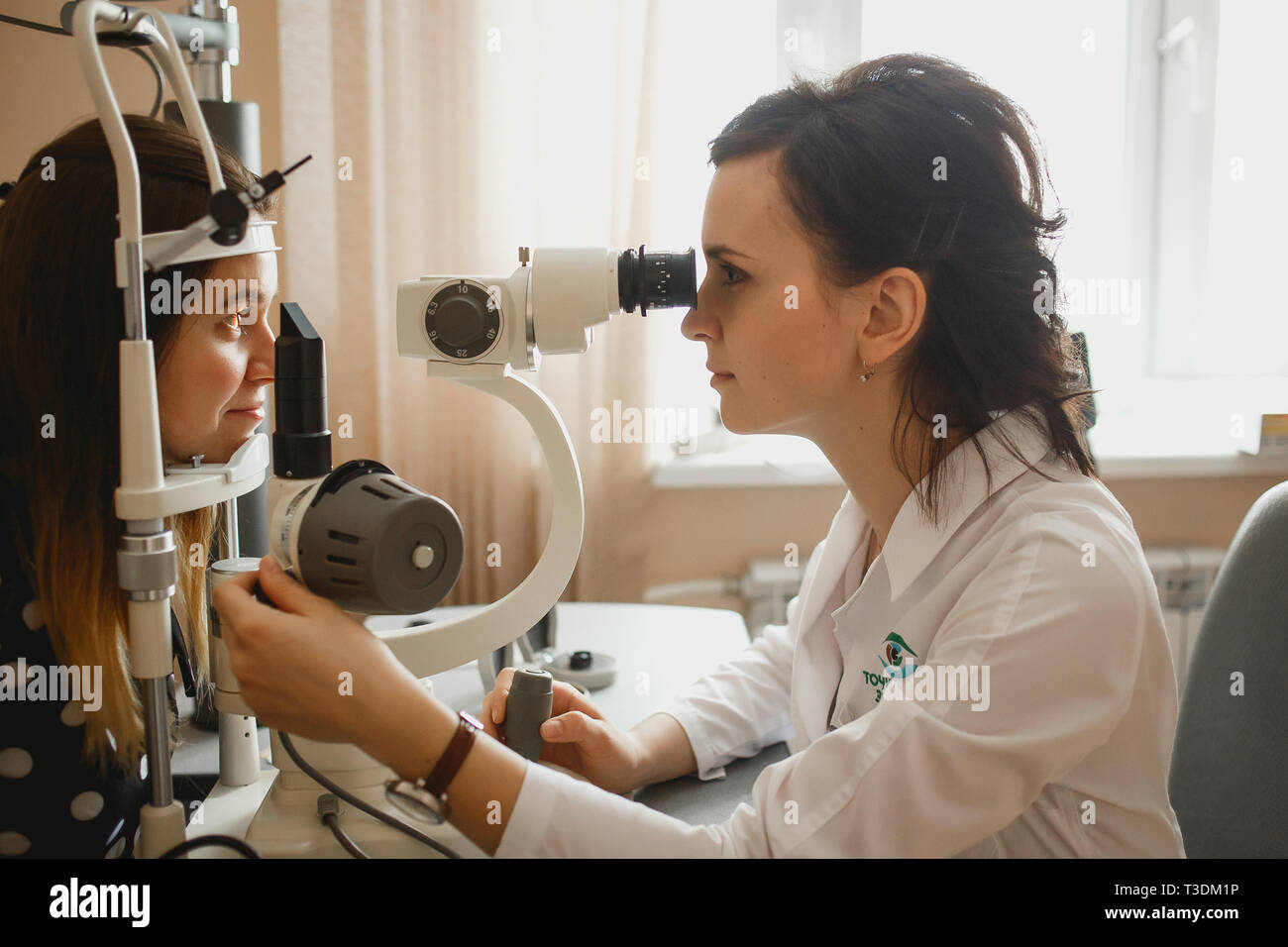 Arkhangelsk, Russia - March 25, 2019: Attractive female doctor ophthalmologist is checking the eye vision of young woman in modern clinic. Doctor and patient in ophthalmology clinic. - Stock Image