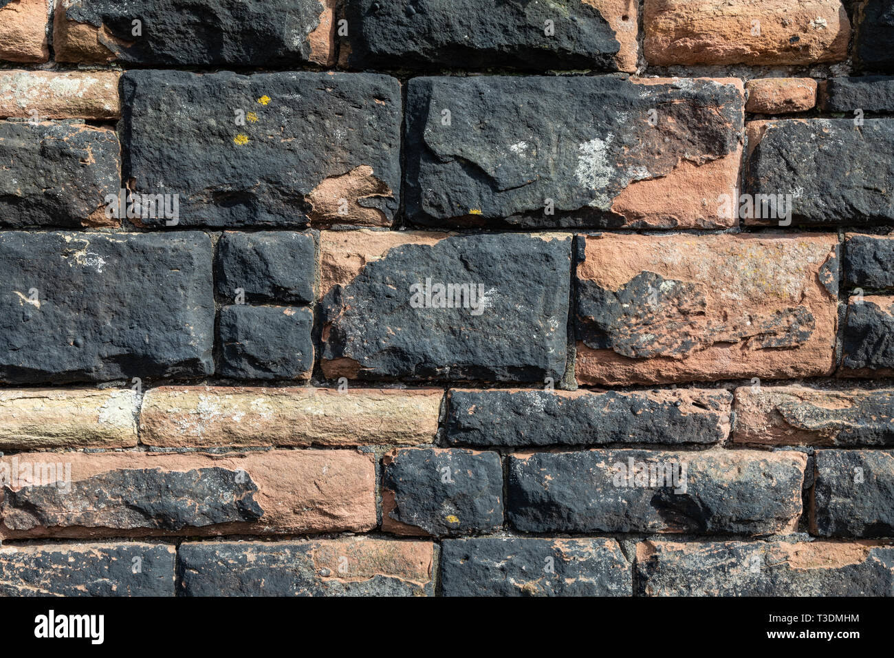Texture of worn and paintedsandstone wall St Helens Merseyside March 2019 Stock Photo