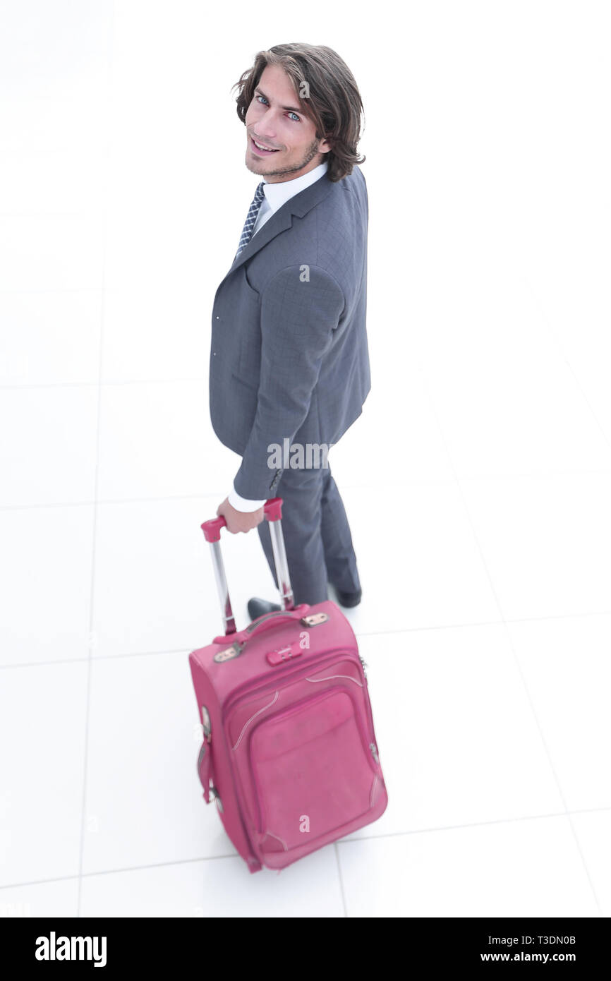 businessman with travel suitcase looking at the camera - Stock Image