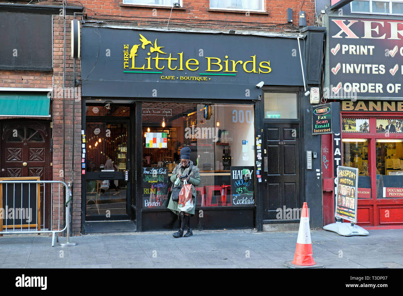 A woman standing outside Three Little Birds Brixton cafe boutique in Coldharbour Lane South London SW9 England UK  KATHY DEWITT - Stock Image